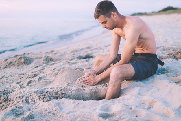 Homem na praia construção castelo de areia