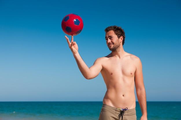 Homem na praia, equilibrando a bola de futebol