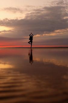 Homem na praia fazendo ioga ou treinando práticas físicas e respiratórias na praia de meadas na natureza em