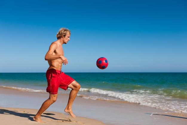 Homem na praia jogando futebol