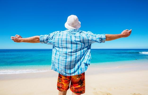 Homem na praia na ilha do havaí. conceito de férias.