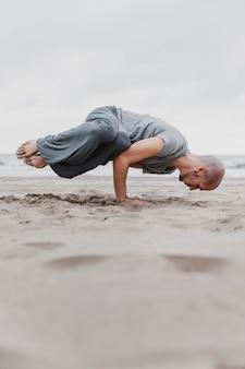 Homem na praia praticando posições de ioga