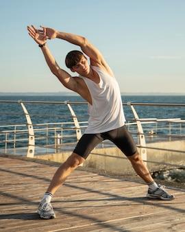 Homem na praia se alongando e se exercitando