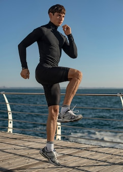 Homem na praia treinando em roupas esportivas