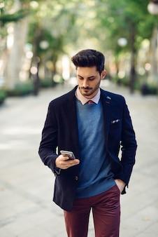 Homem na rua em formalwear com o smartphone na mão.