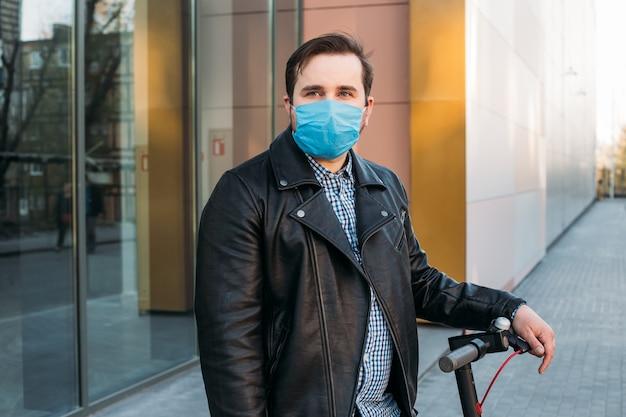Homem na rua usando máscara protetora em scooter elétrico. homem doente com máscara de gripe, conceito de epidemia de gripe na rua.