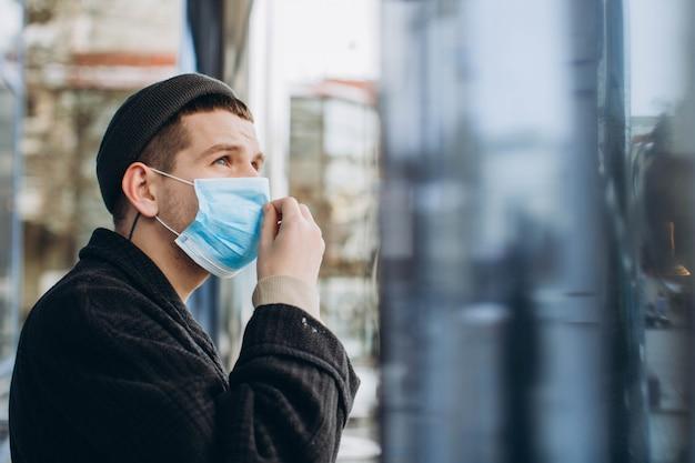 Homem na rua usando máscara protetora.