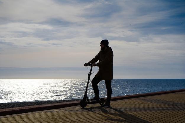 Homem na scooter ao pôr do sol, silhueta, espaço livre