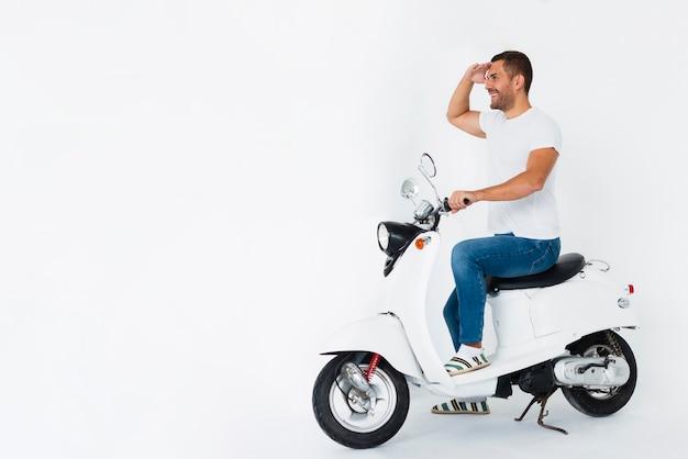 Homem na scooter, olhando para longe