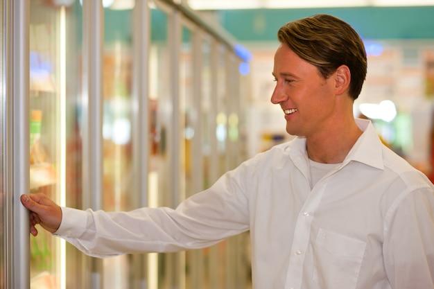 Homem na seção de freezer de supermercado