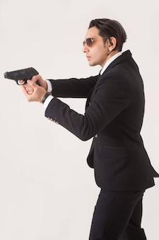 Homem na suíte de negócios e arma no fundo branco