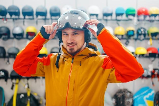 Homem na vitrine experimentando capacete para esqui ou snowboard, vista lateral, loja de esportes.