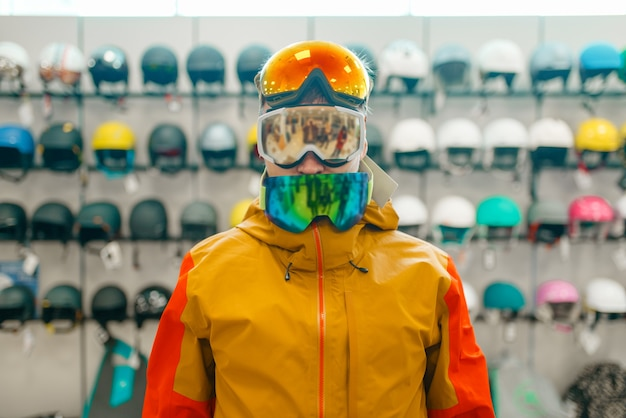 Homem na vitrine experimentando três máscaras para esqui ou snowboard, vista frontal, compras na loja de esportes. estilo de vida extremo na temporada de inverno, loja de lazer ativo, compradores escolhendo equipamentos de proteção