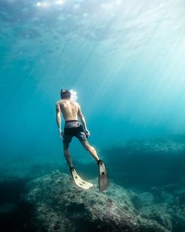 Homem nadando debaixo d'água durante um dia ensolarado