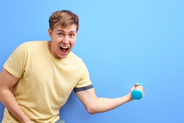 Homem não atlético segurando um pequeno haltere nas mãos, é difícil para ele levantá-lo, gritar, ficar com a boca bem aberta, treinar, bombear os músculos do braço. fundo azul isolado