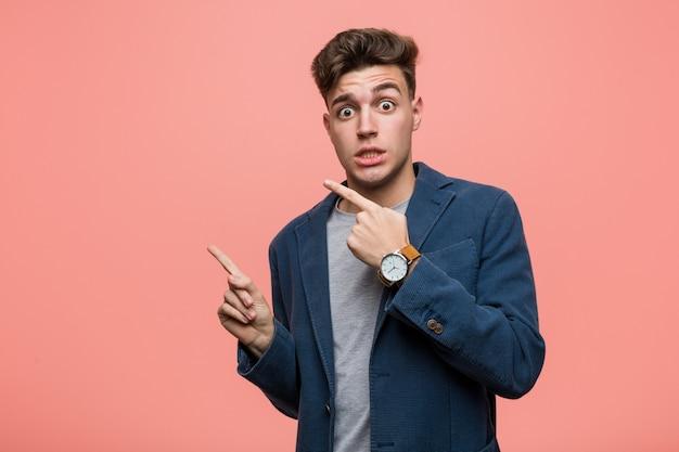 Homem natural de negócios jovem chocou apontando com o dedo indicador para um espaço de cópia.