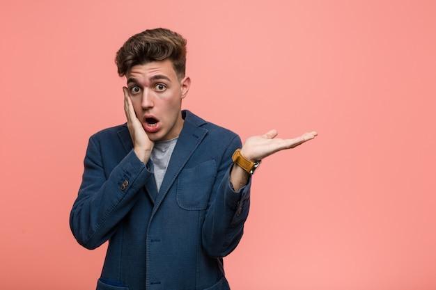 Homem natural de negócios jovem detém cópia na palma da mão, mantenha a mão sobre a bochecha. espantado e encantado.