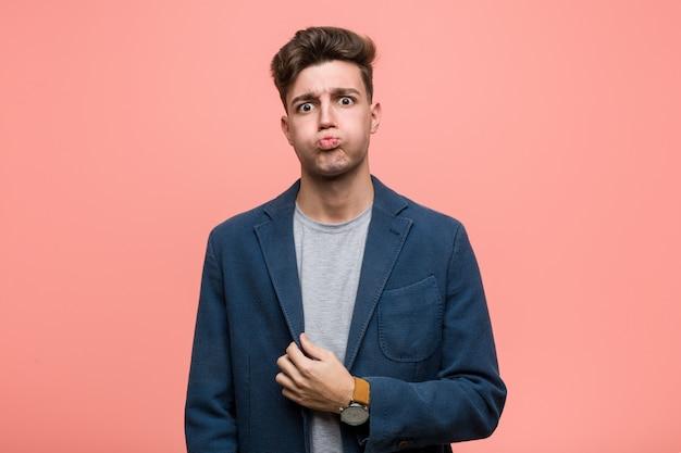 Homem natural de negócios jovem sopra as bochechas, tem expressão cansada. conceito de expressão facial.