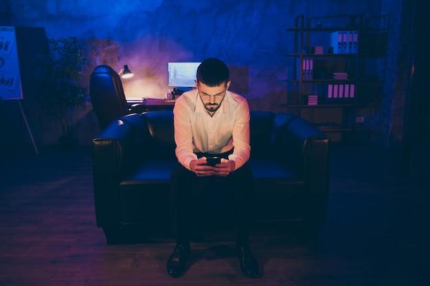 Homem navegando em seu telefone à noite, escritório