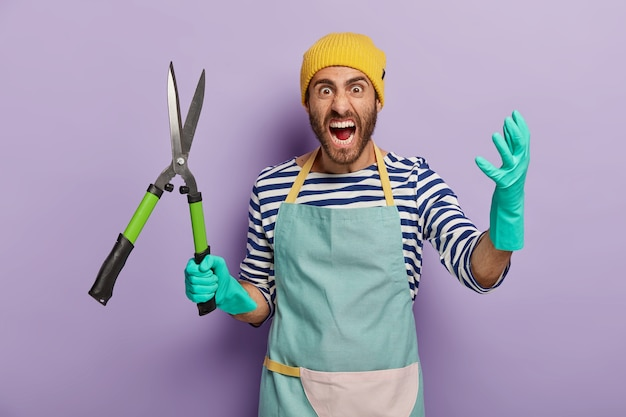 Homem negativo indignado segura tesouras de poda ou tesouras de podar, grita de raiva, trabalha no jardim