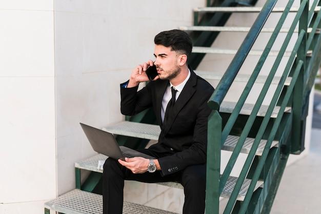 Homem negócio, com, laptop, e, telefone móvel