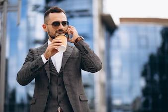 Homem negócio, com, telefone, café bebendo, exterior, arranha-céu