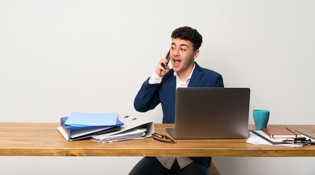 Homem negócio, em, um, escritório, mantendo uma conversa, com, a, telefone móvel