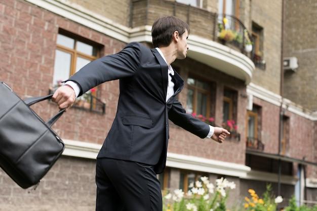 Homem negócio, executando, com, predios, em, fundo