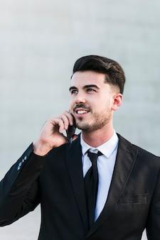 Homem negócio, frente, a, edifício escritório, usando, seu, telefone móvel