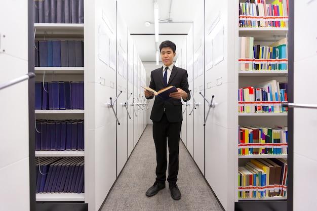 Homem negócio, leitura, segredo, livro, busca, conhecimento, em, um, cofre, locker, biblioteca, sala, com, va