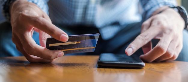 Homem negócio, segurando, cartão crédito, e, usando, smartphone