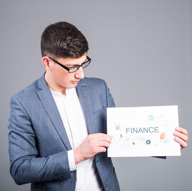 Homem negócio, segurando papel, com, finanças, inscrição