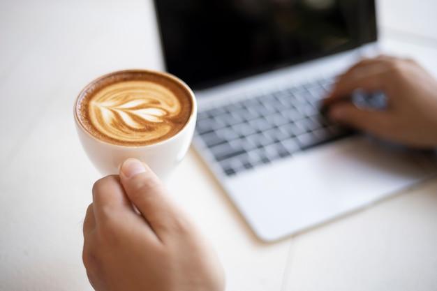 Homem negócio, segurando, xícara café, com, trabalhando, escritório