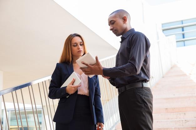 Homem negócio sério, mostrando, colega, tabuleta, tela, ligado, escadas