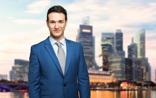 Homem negócio, sorrindo ao ar livre, com, um, modernos, skyline, em, a