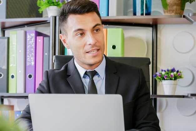 Homem negócio, trabalho, em, modernos, escritório, uso, laptop, computador, e, conversa, alguém, pessoas