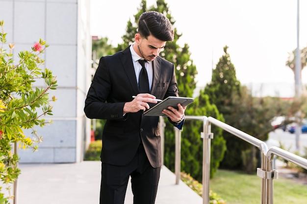 Homem negócio, usando, seu, tabuleta