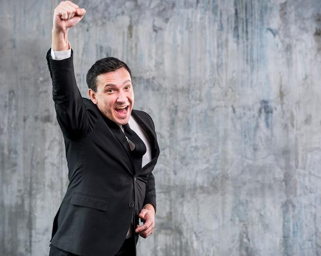 Homem negócios adulto, levantando punho, e, sorrindo