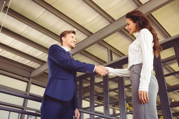 Homem negócios, apertar mão, com, executiva, em, escritório