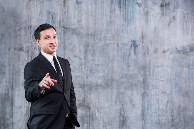 Homem negócios, apontar, câmera, contra, parede cinza