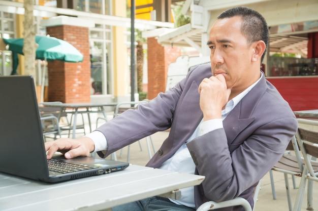 Homem negócios asiático, digitando, ligado, caderno, ou, computador laptop