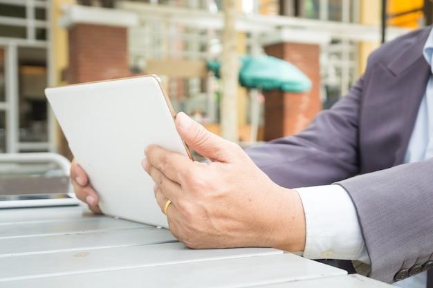 Homem negócios asiático, em, paleto, uso, tablete digital wireless, ao ar livre, em, público