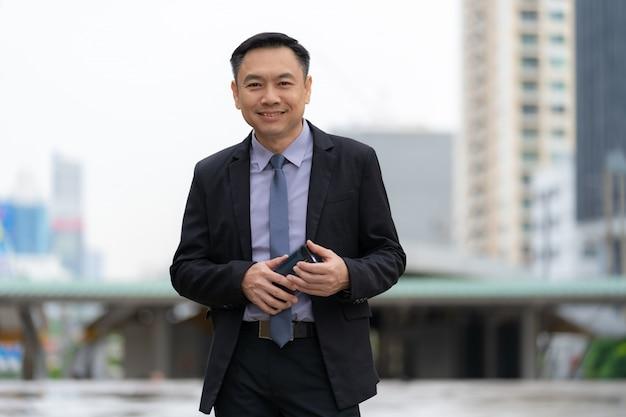 Homem negócios asiático, ficar, e, segurando, telefone móvel