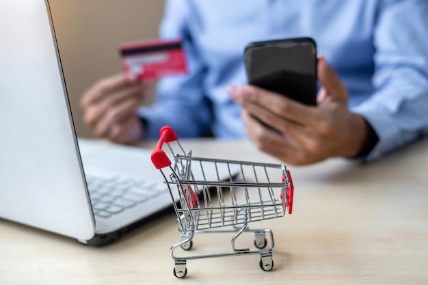 Homem negócios asiático, segurando, cartão crédito, usando, laptop, e, esperto, telefone