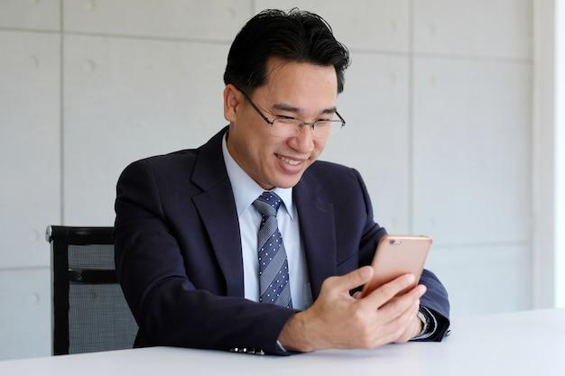 Homem negócios asiático, segurando, esperto, telefone, com, feliz, face sorridente, dentro, escritório eco, predios, b