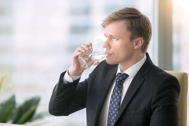 Homem negócios, bebendo, água, escrivaninha