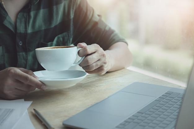 Homem negócios, café bebendo, durante, trabalho, com, laptop