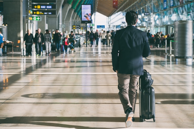 Homem negócios, carregar mala, enquanto, caminhando, um, passageiro, partida terminal