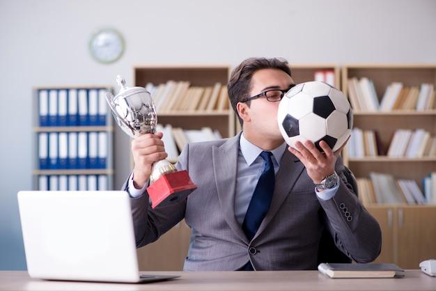 Homem negócios, com, bola futebol americano, em, escritório
