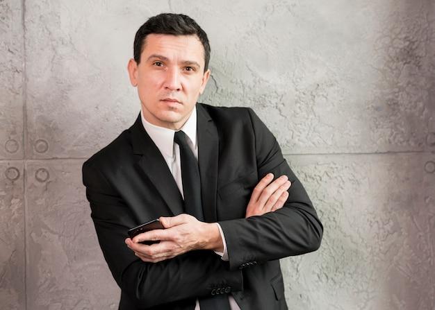 Homem negócios, com, braços cruzados, inclinar-se, parede